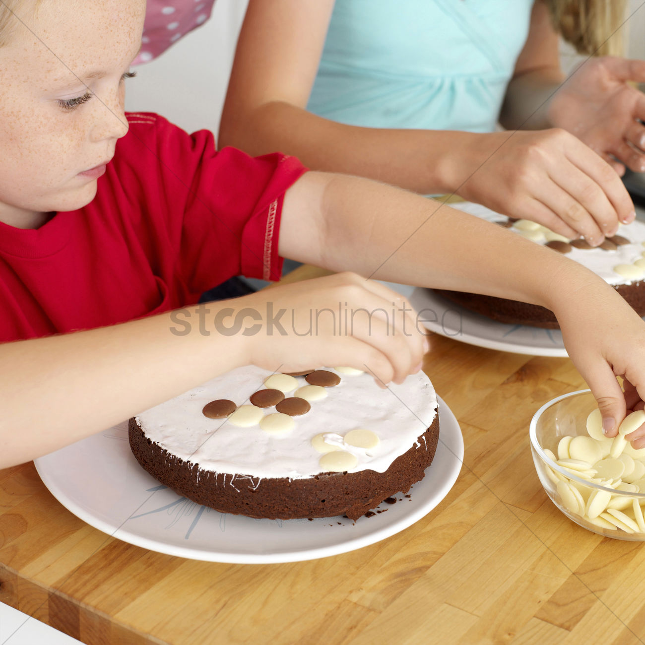 Cake Decorating With Chocolate Candy : Boy and girl decorating cakes with chocolate candies Stock ...
