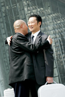 A bald man hugging a bespectacled man