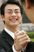 A bespectacled man hand grasping with a guy