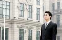 A bespectacled man in business suit standing in front of a building