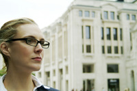 A bespectacled woman standing in front of a building