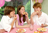 A girl eating together with her two brothers