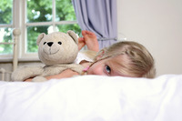 A girl lying forward on the bed with her legs up while hugging her teddy bear