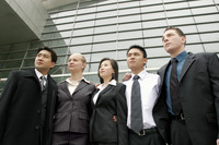 A group of corporate people standing in front of the office building