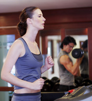 A lady and her boyfriend exercising in a gymnasium