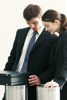 A lady watching as her male colleague opening a briefcase