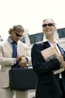 A man and woman in business suit and sunglasses rushing to work