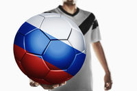A soccer player holding russia soccer ball