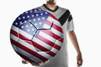 A soccer player holding united states of america soccer ball