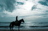 A woman horse riding on the beach