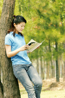 A woman leaning against a tree reading book