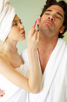 A woman shaving her husband's beard