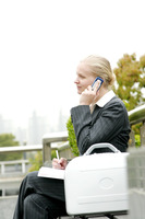 A woman sitting on the bench talking on the hand phone