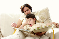 A woman sitting on the couch reading a story book for her young son