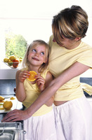 A woman watching her daughter eating a slice of orange