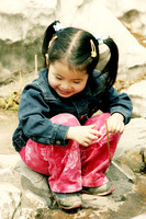 A young girl sitting on the rock