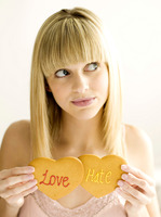A young teen holding two cookies, love and hate