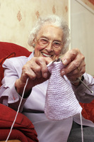 An old bespectacled lady sitting on the couch showing the camera how she knits