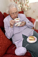 An old bespectacled woman stop knitting for her tea time