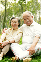 An old couple sitting together on the grass