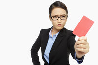 Angry businesswoman holding up  a red card