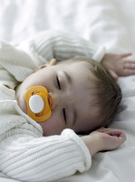 Baby girl sucking on pacifier while sleeping