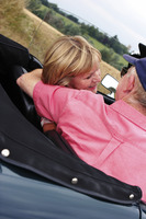 Back shot of an old man placing his hand around his wife's shoulder while sitting in the car