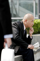 Bald businessman sitting on the bench reading newspaper