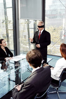 Blindfolded businessman talking in the conference room