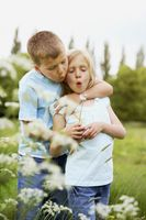 Boy and girl blowing dandelion together