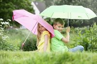 Boy and girl sitting on field holding umbrellas