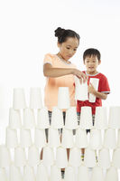 Boy and girl stacking up disposable cups together