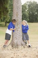 Boy and girl talking beside a tree