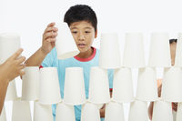 Boy arranging a stack of disposable cups