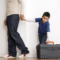 Boy holding his father's hand while trying to carry toolbox