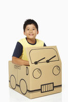 Boy sitting in a cardboard bus, smiling