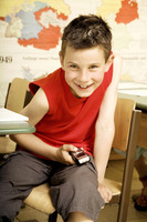Boy text messaging on the mobile phone while sitting in the classroom