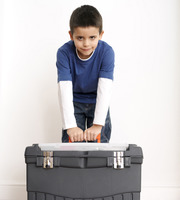 Boy trying to carry up a toolbox