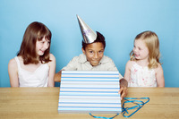 Boy unwrapping present with his friends looking