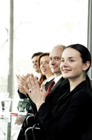 Business people clapping hands while sitting in the conference room