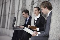Business people sitting at the side of a building