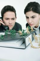 Business people staring closely at toy soldiers on the table