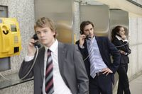 Business people using public telephones