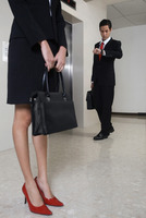 Business people waiting for elevator, businessman checking the time on his watch