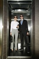 Business people with sunglasses standing in elevator