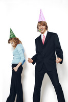 Businessman and businesswoman wearing party hats