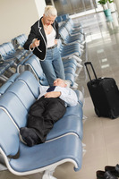 Businessman asleep on seat in airport lounge, businesswoman standing over him pointing finger