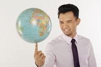 Businessman balancing a globe at the tip of his finger