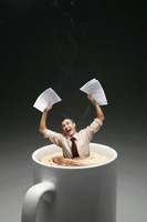 Businessman drowning in a cup of coffee