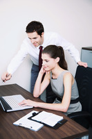 Businessman explaining something to businesswoman using laptop